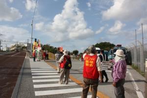 黄色のラインを抗議の市民が1歩でも立ち入らないよう日本の警察官が目を光らせている。参院選前までの黄色のラインは消されて、手前に立っている警察官の右足の下に、かすかに残っている