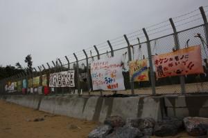座り込みをつづける辺野古のテントと米軍キャンプ・シュワブの境につくられたフェンスには「ジュゴンのうみを壊すな!」「NO BASE」など新基地建設反対の意志表示