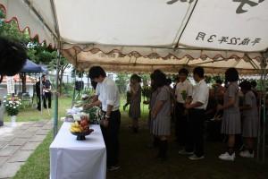 参列した名護高校の生徒たちは菊の花を献花した