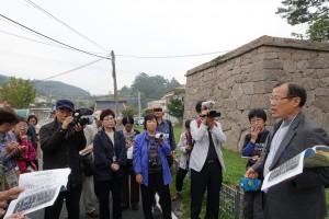 城壁の説明をする朴孟洙さん(右端)
