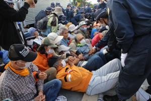 高江のN1ゲート前・オスプレイパッド反対で座り込む人々に全国各地からの警察機動隊が襲いかかり、引き抜き、運ぶ現場