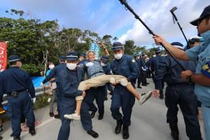 高江のN1ゲート前・建設工事反対で抗議の座り込みの人々に全国各地からの警察機動隊が襲いかかり、引き抜き、運ぶ現場