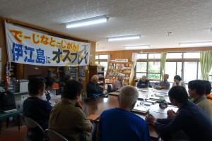 〈「伊江島にオスプレイがきて大変だ」、と訴える横断幕を背に、話をする謝花悦子館長と真剣に耳を傾ける来訪者たち〉