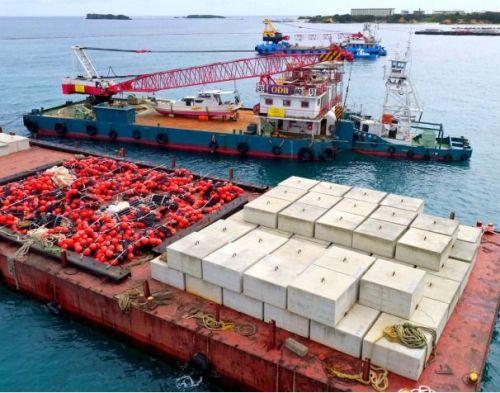 〈大型コンクリートブロックとフロートを積んだ作業船=琉球新報から〉